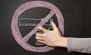 "Hand Holding Chalk Drawn Hand Gun With ""No"" Sign Around It"